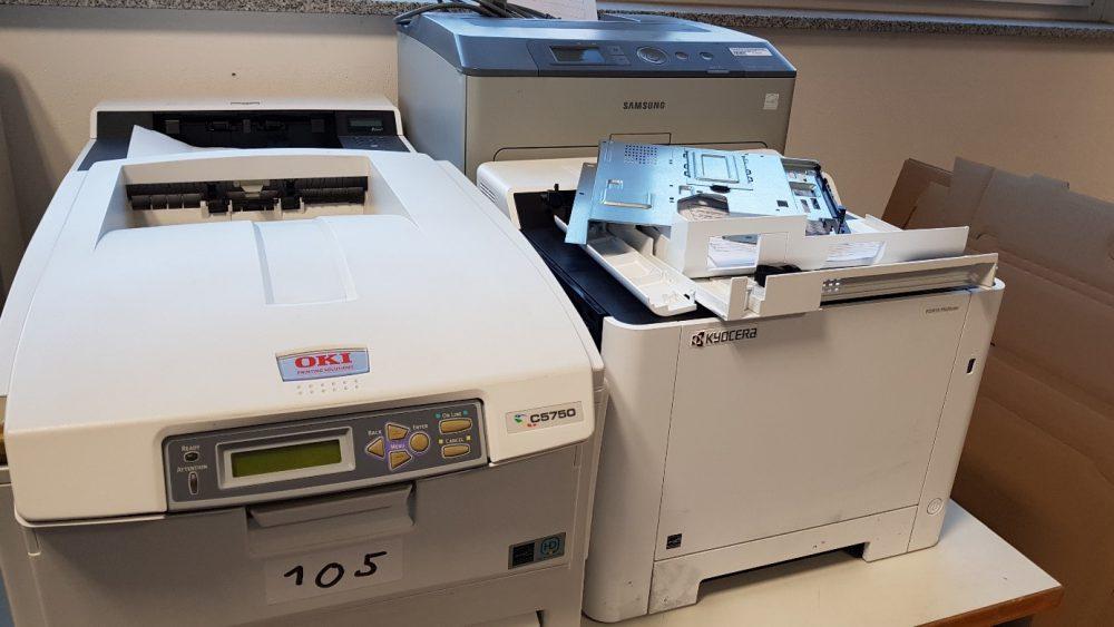 Drei Drucker hinter- bzw. nebeneinander, einer von Oki, einer von Kyocera, einer von Samsung, teilweise auseinandergebaut.