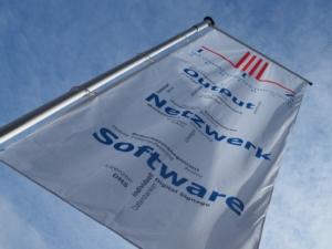 Servicetechniker gesucht - Von schräg unten ist die ITZ Fahne vor blauem Himmel zu sehen. Oben das rotblaue Logo, darunter die einzelnen Kompetenzfelder des ITZ: Output, Netzwerktechnik, Software.